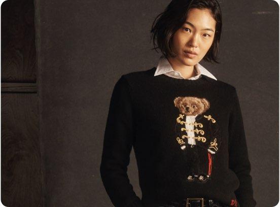 Woman in black sweater large knit Polo Bear motif