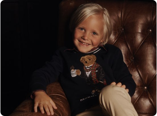 Child in sweater with motif of Polo Bear drinking hot chocolate